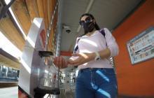 Una usuaria de Transcaribe se aplica gel en las manos una de las estaciones del sistema de transporte masivo de Cartagena.