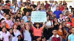Una estudiante sostiene un cartel en respaldo al regreso a clases durante la asamblea multiestamentaria.