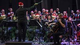 Las víctimas y exmiembros de guerrillas y grupos paramilitares cantan en un coro con la Orquesta Filarmónica de Medellín durante un concierto navideño.