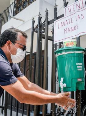 Wadith Enrique Alvarino Aguirre demuestra como funciona su lavadero de manos.