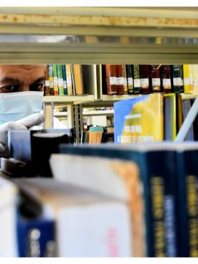 Un usuario recorre uno de los estantes de la Biblioteca Piloto del Caribe.