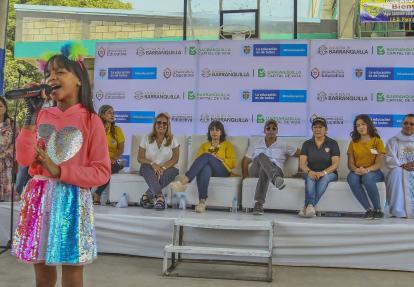 Valentina interpreta una canción en el acto de inauguración. La observan el alcalde Char, la ministra (e) Alarcón, la secretaria Rincón y demás asistentes.