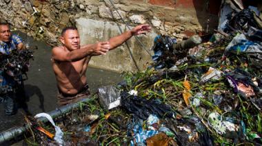 Carlos Tobías, otro afectado por la emergencia limpia el arroyo para que las aguas fluyan.