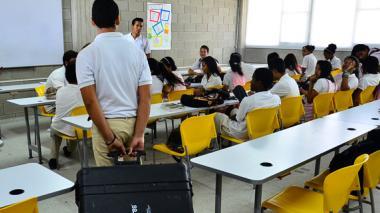 Un estudiante de la escuela Pies Descalzos trae el maletín con los nueve portátiles.