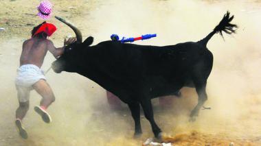 Un toro embiste a un manteador. El hombre se convirtió en el décimotercer herido.