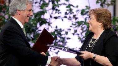 La presidenta chilena, Michelle Bachelet (d) jy su homólogo de Uruguay Tabaré Vázquez firman un acuerdo de cooperación.