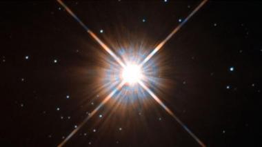 Estrella Próxima Centauri de tonos rojizos, a la cual parece orbitar un nuevo planeta.