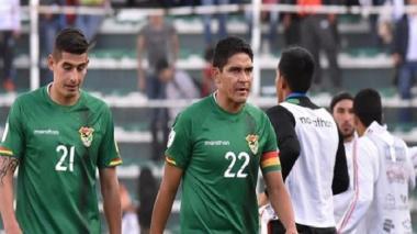 Edward Zenteno (d) y Ronald Eguino, jugadores de la selección boliviana, se retiran decepcionados del campo tras la derrota ante Colombia.
