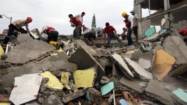 Habitantes de Pedernales y socorristas buscan a víctimas entre las casas destruidas y los escombros.
