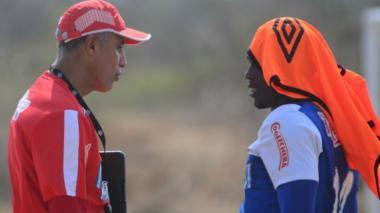 El técnico barranquillero Alexis Mendoza dialoga con el nariñense Édinson Toloza en una práctica del Junior.