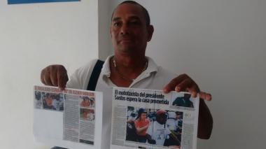 Eliseo Guillén muestra los recortes de los periódicos que publicaron la noticia.