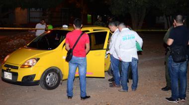 Peritos forenses e investigadores de la Sijín inspeccionan el interior del taxi.