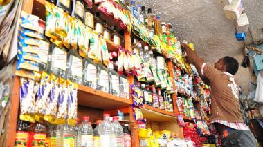 Un ayudante de tienda ubica productos en un estante.