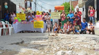 Con pitos, gorros, un pudín y un par de grandes globos dorados, los ciudadanos celebraron el vigésimo quinto aniversario del detrimento del pavimento de las calles de Costa Hermosa.