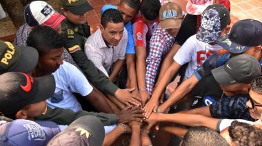 Ex integrantes de la pandilla 'los Pillos' juntan las manos con dos policías, en señal de unión y compromiso.