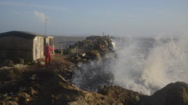 Un hombre pesca sobre el enrocado de Bocas de Ceniza. A un lado, el fuerte oleaje.