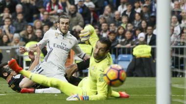 El delantero galés del Real Madrid, Gareth Bale, marca un gol en la portería de Diego López, del Espanyol durante el partido correspondiente a la jornada 23.