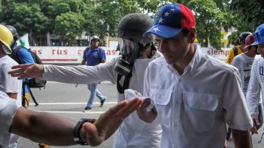 El líder opositor venezolano Henrique Capriles es guiado por manifestantes.