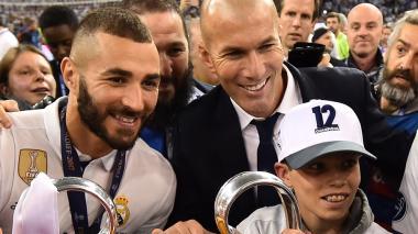 Karim Benzema (i) posa con Zinedine Zidane (d) y el trofeo de la Champions League.