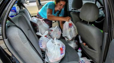 La ciudadana Nuris Pérez guarda las bolsas con la compra del mercado.