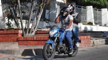 El conductor de una moto transporta a un parrillero, lo cual está prohibido por el decreto.