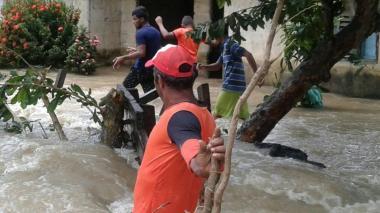 Personas caminan en medio de las inundaciones.