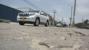 Un vehículo esquiva uno de los tramos dañados en la Vía 40 con calle 85.