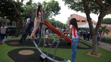 Niños se divierten en zona de juegos infantiles.