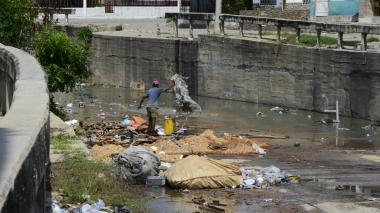 La imagen muestra a un hombre en el canal de Rebolo, a la altura de la calle 27 con carreras 25 y 25A, cuando manipula los desechos arrojados por un tercero.