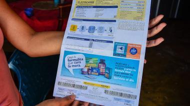 Un habitante de Villa Zambrano muestra su factura del servicio de energía eléctrica.