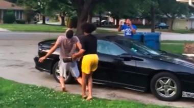 Captura de video en la que una niña vierte agua caliente sobre un adulto que está lavando su carro.