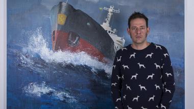 El artista visual Juan Mejía frente a una de sus piezas expuestas.
