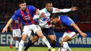 James Sánchez intenta eludir la marca de dos jugadores del Cerro Porteño.