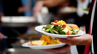 Un mesero lleva en sus manos platos de comida.