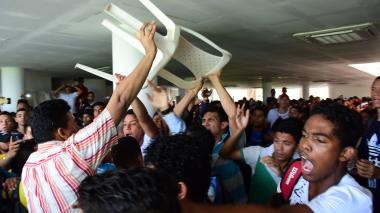 Un estudiante levanta una silla para lanzarla en medio de la protesta del jueves en Uniatlántico.