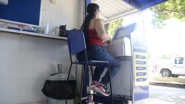 Una vendedora de chance atiende el punto de venta sin uniforme, en El Bosque.