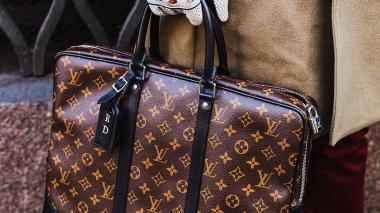 Una mujer sostiene un bolso Louis Vuitton.