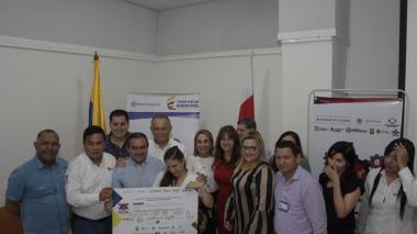 Kelly Johana Landinez, en compañía de funcionarios de la Gobernación y las alcaldías de Barranquilla y Soledad, muestra el documento simbólico del acuerdo.