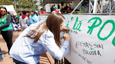 Karen Abudinen, directora nacional del Icbf, anota un mensaje en un cartel para decir: ¡No a la pólvora!.