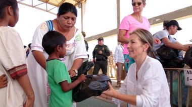 La primera dama de la Nación, Clemencia De Santos, le entrega un obsequio a un niño.