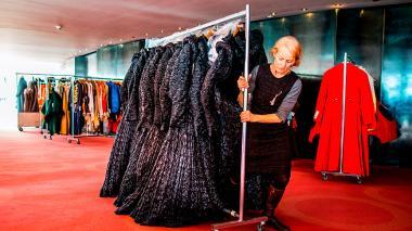 Una mujer arregla de la Ópera Nacional de Asmterdam arregla algunos de los vestidos subastados este sábado.