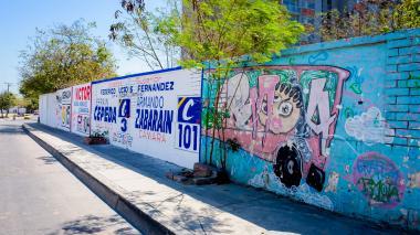 Varias publicidades de candidatos políticos donde antes existían grafitis, en la entrada de Soledad 2000.