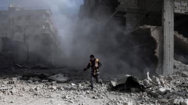 Un voluntario de la Defensa civil, conocido como White Helmets, revisa el sitio de un ataque aéreo del régimen en la ciudad de Saqba, en la sitiada región oriental de Ghouta, en las afueras de la capital, Damasco.