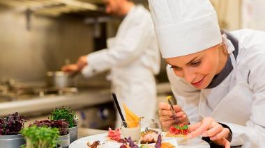 Una chef ensambla, con suma delicadeza, un plato de alta cocina.