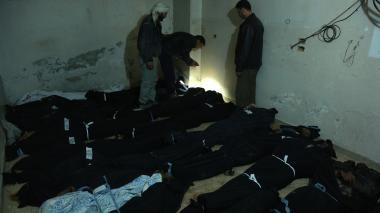 Tres hombres en labores de identificación de cadáveres en una morgue improvisada en un hospital en Douma, después de los bombardeos del gobierno sirio.