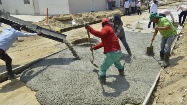 Hombres realizan trabajo de pavimentación.