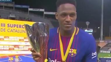 El defensor colombiano Yerry Mina levanta el trofeo de campeón de la