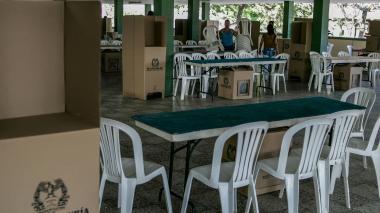 Una mujer carga dos sillas para organizar el espacio de votación del Centro Social Don Bosco.