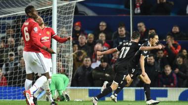 El francés Ben Yeder corre a celebrar el primer gol del Sevilla, mientras dos jugadores del Manchester United y el público se lamentan.