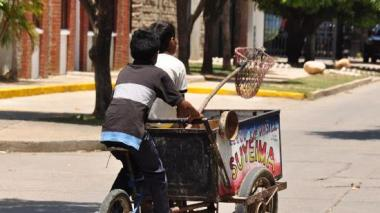 Dos niños venden agua sobre una bicicleta.